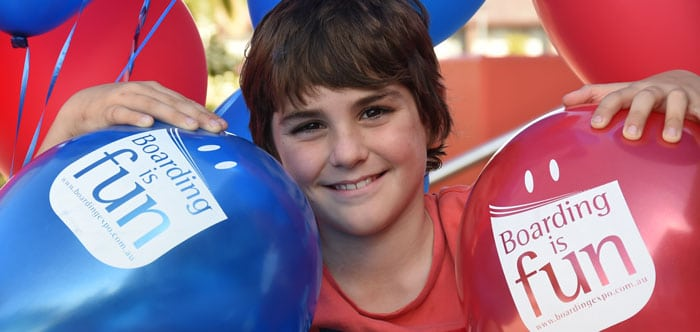 "Close up of boy holing Expo balloons, with graphic ""Boarding is Fun!"""